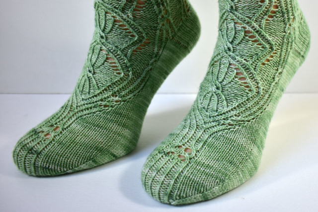 Foot detail of Triforium sock pattern with cables and lace