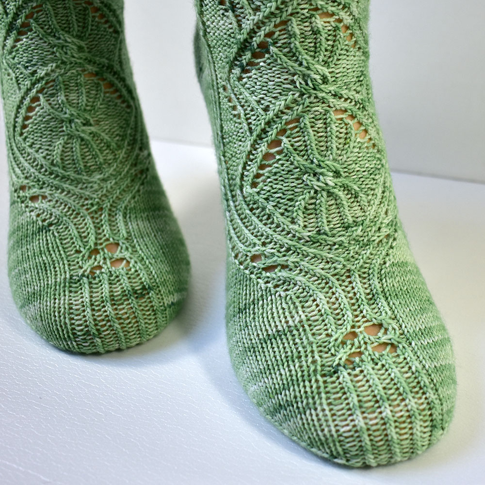 Toe detail of the triforium sock pattern with cables and lace